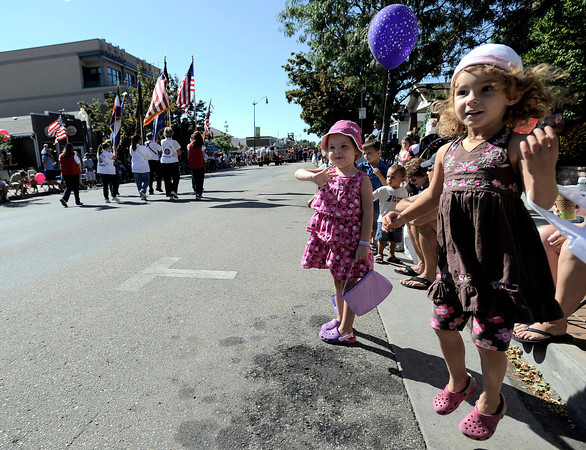 Makayla Heron (right), 4, jumps with excitement and Lacy Thompson (left), 4, waves as  the Louisville Labor Day Parade passes by in Louisville, Colorado September 5, 2011.   CAMERA/Mark Leffingwell