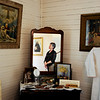 "Bridget Bacon, Louisville Historical Museum Coordinator, is reflected in the mirror while talking about the furnishings in the bedroom of the miner's cottage.<br /> The Louisville Historical Museum celebrates 25-years in existence.<br /> For  more photos and a video of the museum, go to  <a href=""http://www.dailycamera.com"">http://www.dailycamera.com</a>.<br /> Cliff Grassmick / September 22, 2011"
