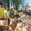 32nd annual Acre Cleanup run by CBA at North Common. From left, James Ostis, Vanna Howard and Francisca Sierra of Lowell and Jen Myers of Dracut, with the yard waste collected. (SUN/Julia Malakie)