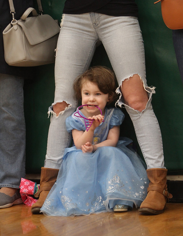 . Lowell Catholic pre-prom procession at the gym. Addison Feeney, 3, of Lowell, whose mother coaches at Lowell Catholic, watches the parade of prom couples. (SUN/Julia Malakie)