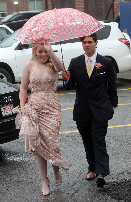. Lowell Catholic pre-prom procession at the gym. Brenna Riley and George Zuleta Jr. arrive in a light rain. (SUN/Julia Malakie)