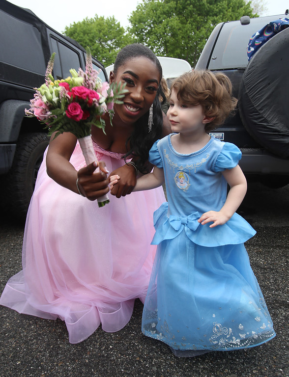 . Lowell Catholic pre-prom procession at the gym. Patricia Adesanya of Lowell with Addison Feeney, 3, of Lowell, daughter of Adesanya\'s soccer, track and lacrosse coach. (SUN/Julia Malakie)