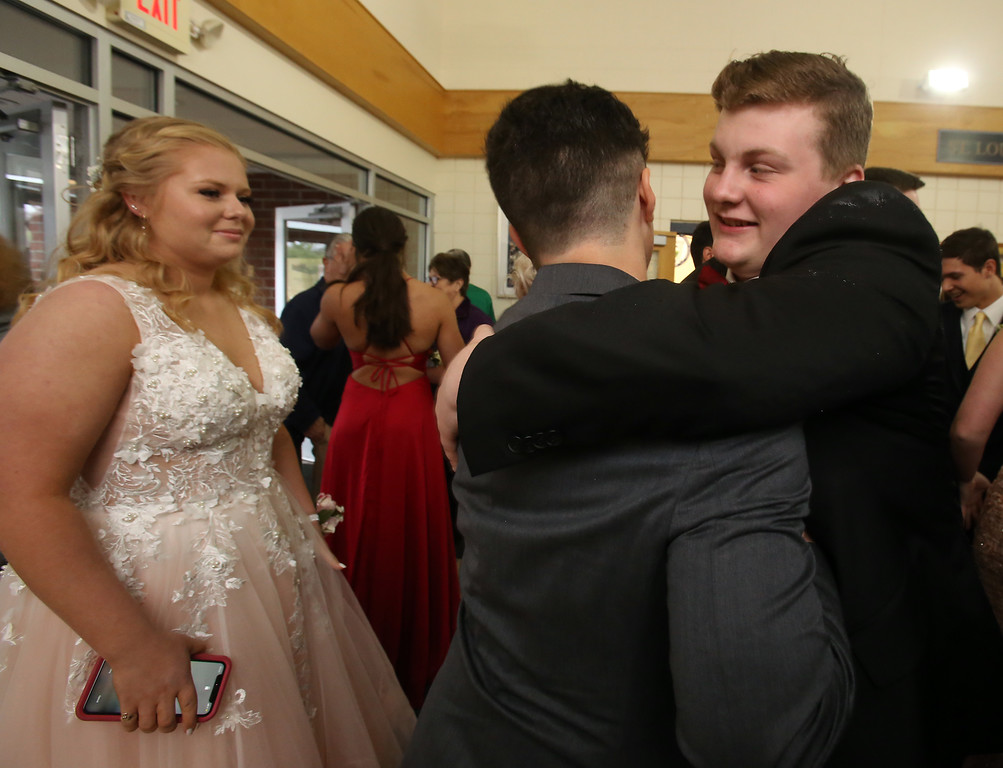 . Lowell Catholic pre-prom procession at the gym. James Giblin, right, hugs Nic Pereira, as Pereira\'s date Kylee Jedraszek looks on. (SUN/Julia Malakie)