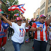 First night of Lowell Folk Festival. Parade to Boarding House Park and opening ceremony. Lily Pagan, left, and Betsy St. Onge, both of Lowell with Puerto Rican group in parade. (SUN/Julia Malakie)