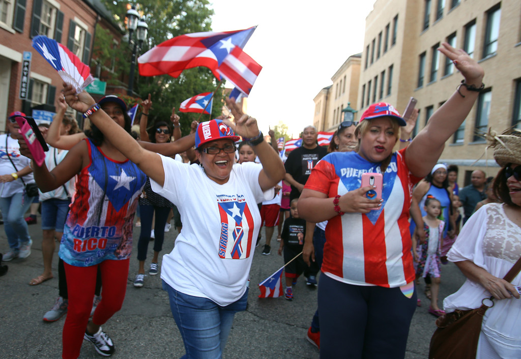 . First night of Lowell Folk Festival. Parade to Boarding House Park and opening ceremony. Lily Pagan, left, and Betsy St. Onge, both of Lowell with Puerto Rican group in parade. (SUN/Julia Malakie)