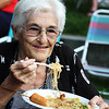 First night of Lowell Folk Festival. Parade to Boarding House Park and opening ceremony. Mary Lou Pasini of Groton eats Laotian food at Boarding House Park. (SUN/Julia Malakie)