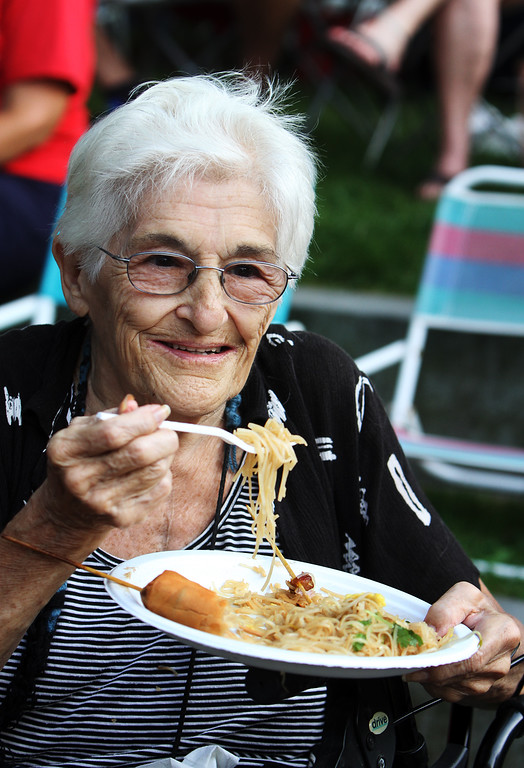 . First night of Lowell Folk Festival. Parade to Boarding House Park and opening ceremony. Mary Lou Pasini of Groton eats Laotian food at Boarding House Park. (SUN/Julia Malakie)