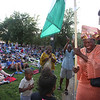 First night of Lowell Folk Festival. Parade to Boarding House Park and opening ceremony. Meg Moweto of Billerica carries the Nigerian flag. (SUN/Julia Malakie)