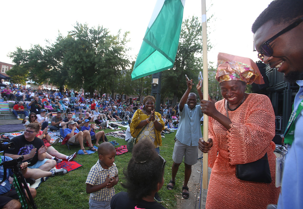. First night of Lowell Folk Festival. Parade to Boarding House Park and opening ceremony. Meg Moweto of Billerica carries the Nigerian flag. (SUN/Julia Malakie)