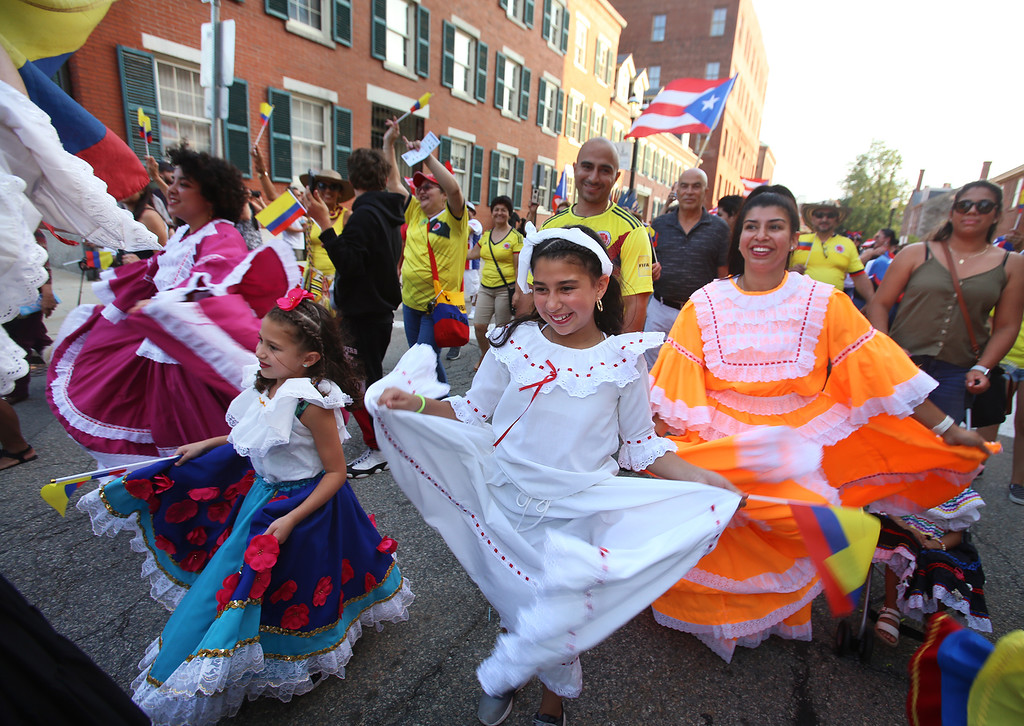 . First night of Lowell Folk Festival. Parade to Boarding House Park and opening ceremony. From left front, Analia Naranjo, 6, her sister Ariana Naranjo, 10, and their mother Alisson Naranjo of Lowell, in parade with Colombian group.  (SUN/Julia Malakie)