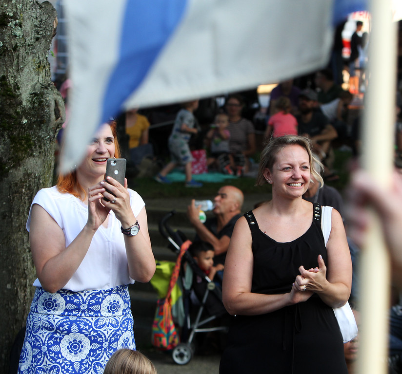 . First night of Lowell Folk Festival. Parade to Boarding House Park and opening ceremony. Jennifer Banks of Littleton, left, and her friend Pamela Kopsiaftis of Lowell watch opening parade at Boarding House Park. (SUN/Julia Malakie)