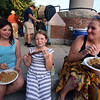 First night of Lowell Folk Festival. Parade to Boarding House Park and opening ceremony. From left, Nevaeh McGrath, 12, her sister Chloe McGrath, 8,  and their mother Colleen McGrath of Lowell eat Laotian food at Boarding House Park. (SUN/Julia Malakie)