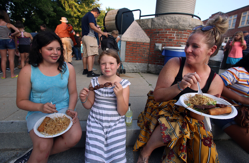 . First night of Lowell Folk Festival. Parade to Boarding House Park and opening ceremony. From left, Nevaeh McGrath, 12, her sister Chloe McGrath, 8,  and their mother Colleen McGrath of Lowell eat Laotian food at Boarding House Park. (SUN/Julia Malakie)