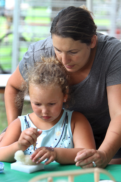 . Saturday at Lowell Folk Festival. Scarlett Edward, 7, of Andover, works on needle felting a bird as her mother Megan Edward watches. (SUN/Julia Malakie)