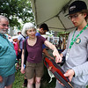 Saturday at Lowell Folk Festival. From left, David Salomon and his wife Marilyn Leeds of Acton listen as Josh Webb of Arlington demonstrates the Cricket violin made by his family's company Magic Fluke, whose stringed instruments resemble the tail of a whale. (SUN/Julia Malakie)