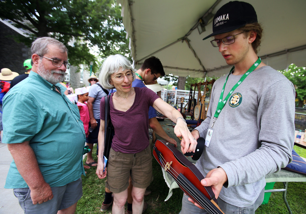 . Saturday at Lowell Folk Festival. From left, David Salomon and his wife Marilyn Leeds of Acton listen as Josh Webb of Arlington demonstrates the Cricket violin made by his family\'s company Magic Fluke, whose stringed instruments resemble the tail of a whale. (SUN/Julia Malakie)