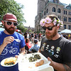 Saturday at Lowell Folk Festival. Marc Mastrolia of Lowell, left, and Andrew Correia of Chelmsford eat Greek food at JFK Plaza.  (SUN/Julia Malakie)