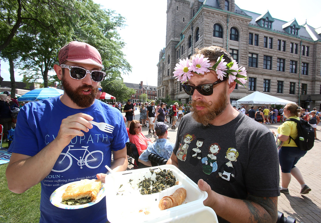 . Saturday at Lowell Folk Festival. Marc Mastrolia of Lowell, left, and Andrew Correia of Chelmsford eat Greek food at JFK Plaza.  (SUN/Julia Malakie)