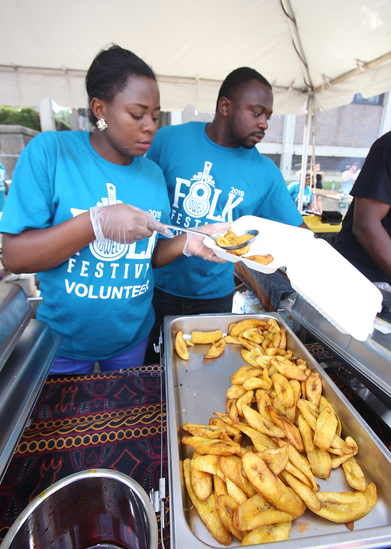 . Saturday at Lowell Folk Festival. Gillian Amin and Vitalis Forchap, both of Andover, serve Cameroonian food, including plantains, at JFK Plaza. (SUN/Julia Malakie)