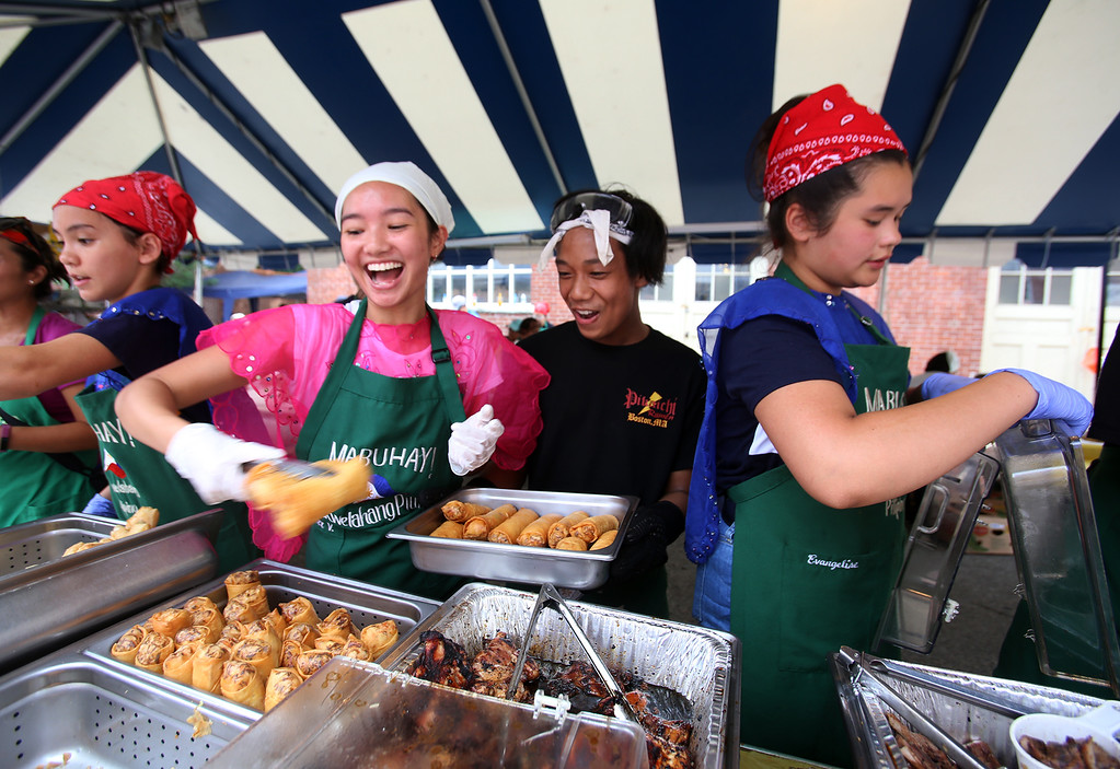 . Saturday at Lowell Folk Festival. From left serving Pilipino food: Emma Lane-Smith, 12, of Westford, Ceci Villasenor, 19, of Acton, Max Bolandrina, 15, of Douglas, and Eva Janairo, 13, of Newton. (SUN/Julia Malakie)