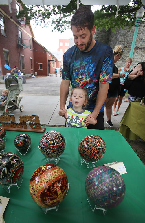. Saturday at Lowell Folk Festival. Terrian Odeneal, 3, and her father Cayce Odeneal of Lowell look at Ukrainian pysanky (Easter egg painting) made by Father Paul Luniw of Terryville, Conn. (SUN/Julia Malakie)