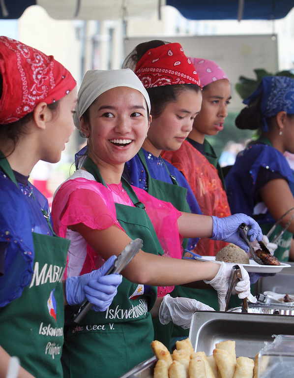. Saturday at Lowell Folk Festival. From left serving Pilipino food: Emma Lane-Smith, 12, of Westford, Ceci Villasenor, 19, of Acton, and Eva Janairo, 13, of Newton. (SUN/Julia Malakie)