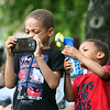 Saturday at Lowell Folk Festival. Samuel Tugbiyele, 6, of Lowell, left, photographs Grupo Cimarron at Boarding House Park as his brother Ellis Tugbiyele, 4, cools him off with a portable fan. (SUN/Julia Malakie)