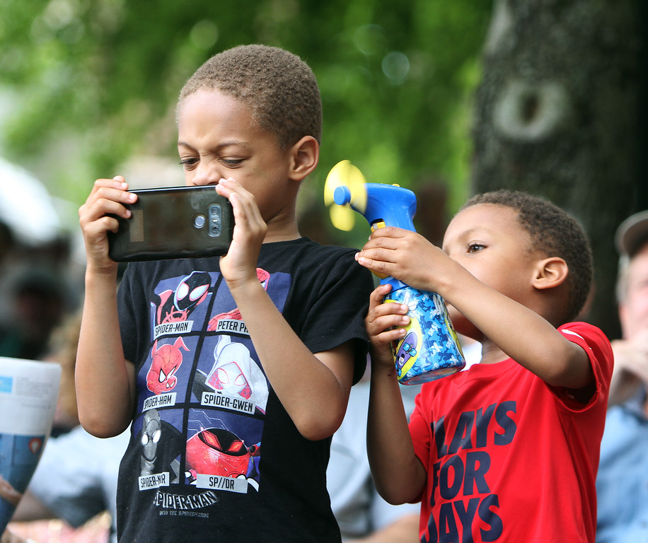 . Saturday at Lowell Folk Festival. Samuel Tugbiyele, 6, of Lowell, left, photographs Grupo Cimarron at Boarding House Park as his brother Ellis Tugbiyele, 4, cools him off with a portable fan. (SUN/Julia Malakie)