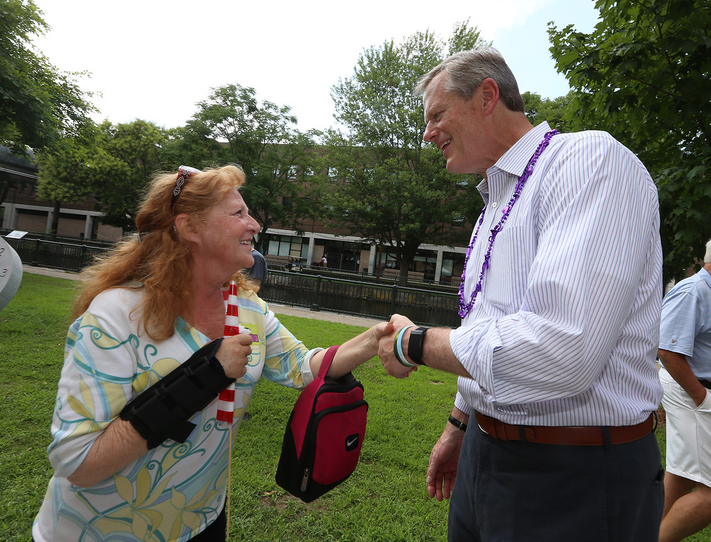 . Lowell Folk Festival. Sandra Arcand of Lowell greets Gov. Charlie Baker, whom she likes a lot, in Lucy Larcom Park. (SUN/Julia Malakie)