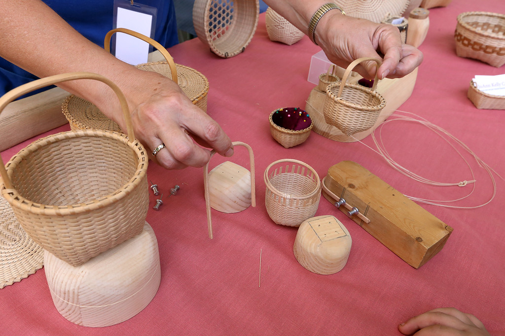 ". Lowell Folk Festival. JoAnn Kelly Catsos, Black Ash Splint Basketmaker, holds a ""kitten\'s head\"" basket, a smaller version of the \""cat\'s head\"" basket at left, so called because of the points on the bottom. (SUN/Julia Malakie)"
