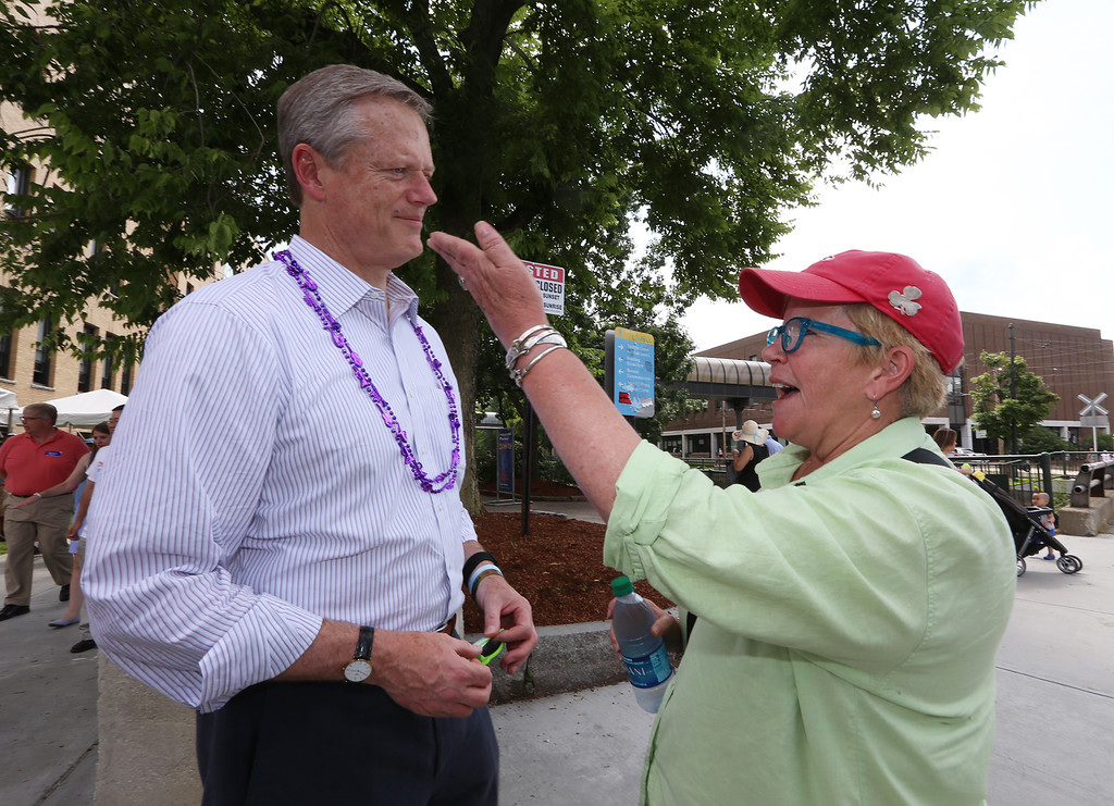 . Lowell Folk Festival. Lowell High art teacher Katy Sheridan of Lowell greets Gov. Charlie Baker as he was passing by her classroom on the corner of Lucy Larcom Park and French Street. (SUN/Julia Malakie)