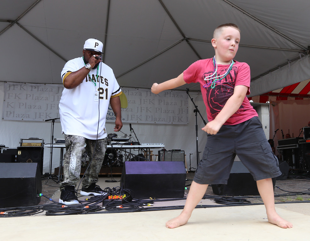 . Lowell Folk Festival. Beatboxing master Rahzel invites Thomas Shay, 8, of Lowell, onstage to dance at JFK Plaza. Shay was doing \'the floss.\' (SUN/Julia Malakie)