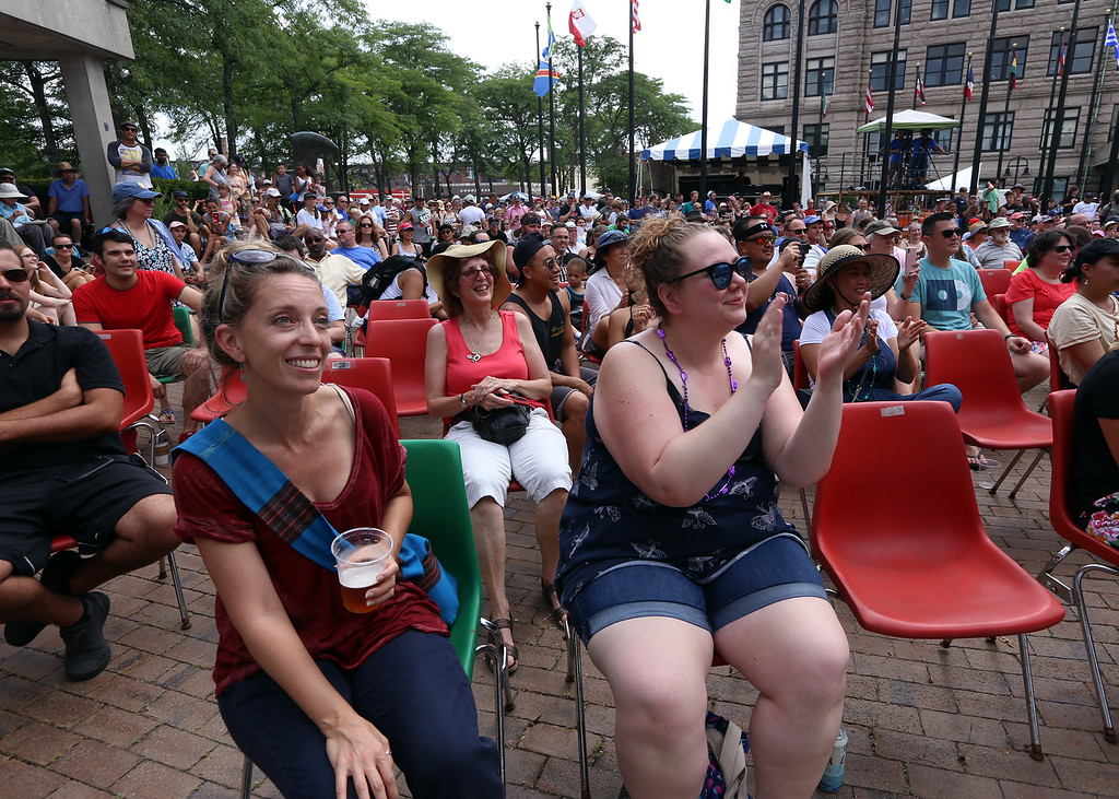 . Lowell Folk Festival. Rachel Greenberger of Somerville, left, and Katie Ryan of Braintree, listen to beatboxing master Rahzel at JFK Plaza. (SUN/Julia Malakie)