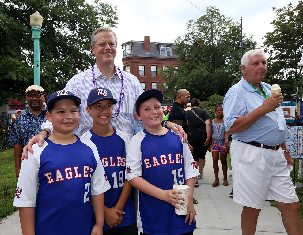 . Lowell Folk Festival. Gov. Charlie Baker stops for a photo with baseball players during a walk through the Folk Festival. City manager Eileen Donoghue\'s husband John O\'Connor, right. (SUN/Julia Malakie)