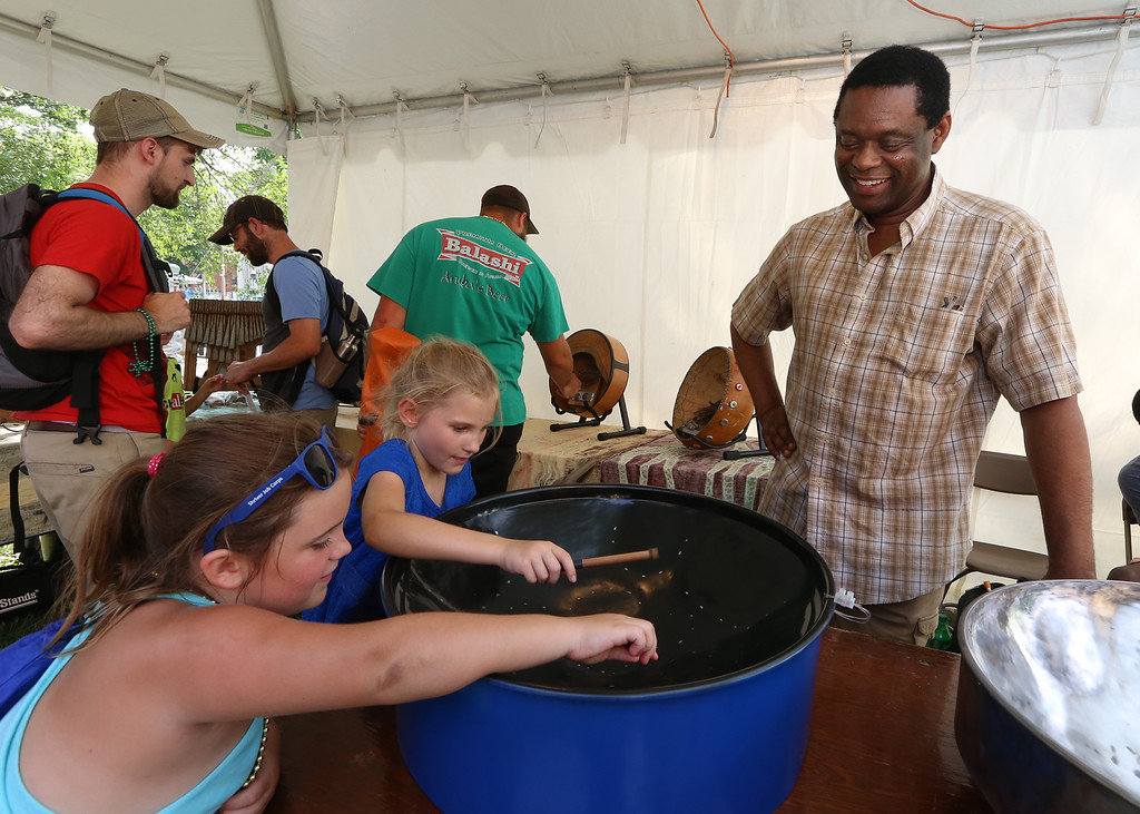 . Lowell Folk Festival. Adrie Greenwood, left, and her friend Kalina Martinage, both 7 and from Dunstable, try playing a steel pan drum at the booth of Zimbabwean musician Solomon Murungu of Belmont. (SUN/Julia Malakie)