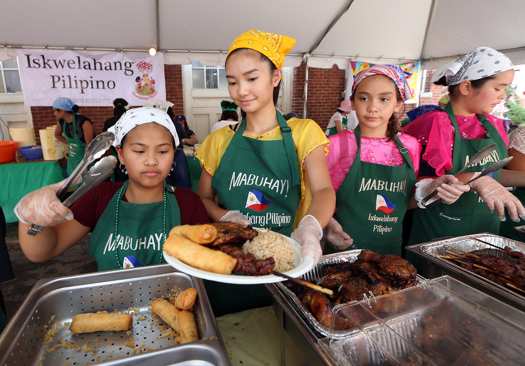 . Lowell Folk Festival. From left, Reyna Jane Javier, 10, of Dracut, Ceci Villasenor, 18, of Acton, Emma Lane-Smith, 11, of Westford, and Eva Janairo, 12, of Newton, serve food at the Iskwelahang Pilipino tent on French Street. (SUN/Julia Malakie)