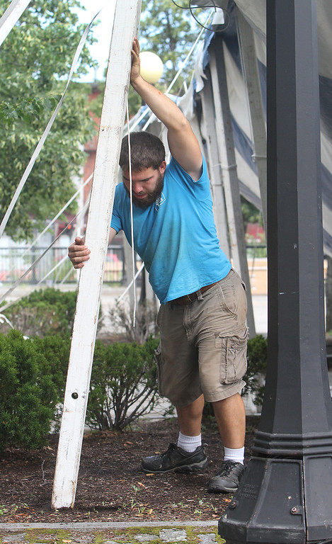 . Workers from Commercial Tent Rentals in New Brunswick set up the tent for the Dutton Street Dance Pavilion. Tim Levy of Norton, N.B., pushes a pole in place. Levy met his wife at the Lowell Folk Festival four years ago. (SUN/Julia Malakie)
