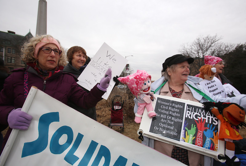 Rally for Women organized by Solidarity Lowell, at the Ladd & Whitney Monument. Susan Graves of Chelmsford, left, and Linda Copp of North Chelmsford, front right. (SUN/Julia Malakie)