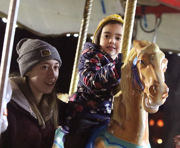 Opening night of Lowell WinterFest 2020. Allora Rudy, left, and her sister Ember Rudy, 4, of Lowell, ride the carousel.  (SUN/Julia Malakie)