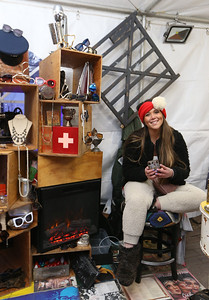Opening night of Lowell WinterFest 2020. Ashley Boiardi of Saugus, owner, with her sister, of AshBmarie.com popup business which sells new accessories and small antique items, stays warm by a portable electric fireplace in her tent. (SUN/Julia Malakie)