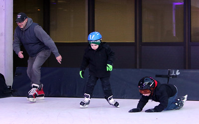 Opening night of Lowell WinterFest 2020. Chris Graceffa of Lowell skates with his sons Luke Graceffa, 5, center, and John Graceffa, 6, on the artificial ice at JFK Plaza. (SUN/Julia Malakie)