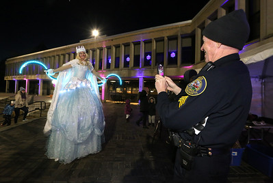 Opening night of Lowell WinterFest 2020. Lowell Police Sgt. Tom Hultgren takes a photo of Talia the Snow Princess (Liz Knights of Lowell, with Cirque de Light). (SUN/Julia Malakie)