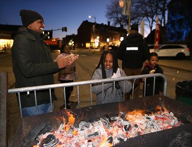 Opening night of Lowell WinterFest 2020. Julius Wakaba of Lowell keeps warm by the fire as daughters Talia Njui, 10, rear, Imani Njui, 9, and Bella Wakaba, 6, eat toasted marshmallows. (SUN/Julia Malakie)