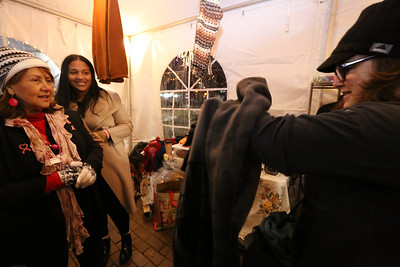 Opening night of Lowell WinterFest 2020.  From left, Maria Vejar of Dracut, owner of Galeria De Los Andes, and employee Ashley Morales of Lowell, watch as Carole Sweeney of Dracut puts on an alpaca poncho that her son had just bought her for her birthday. (SUN/Julia Malakie)