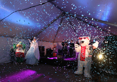 Opening night of Lowell WinterFest 2020. Confetti is released at opening ceremony. From left, the Canaligator, Talia the Snow Princess (Liz Knights of Lowell, with Cirque de Light), Lowla, and volunteer Abby Petrucci of Ashby.  (SUN/Julia Malakie)