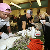2019 Lowell Winterfest. From left, Chay Pin of Lowell chops up noodles, Lao' De Cafe owner Ricky Rathsombath of Lowell prepares a serving of Chicken Coconut Curry for Carie Mansinon of Nashua. (SUN Julia Malakie)