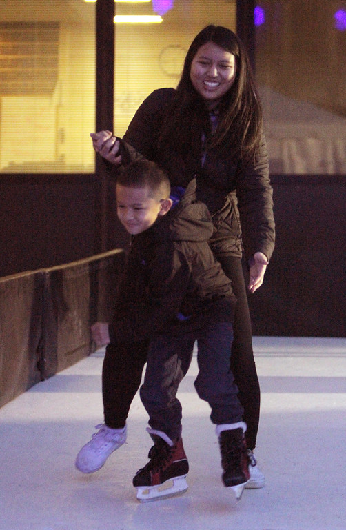 . Lowell Winterfest opening night. Selena Phang, 18, and her nephew Toby Bong, 5, both of Lowell, skate on the artificial ice at the Civic Center. (SUN Julia Malakie)