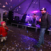 Lowell Winterfest opening night. Audrey Lavoie, 2, of Lowell, enjoys the confetti her father Brian Lavoie tossed at the JFK Plaza music tent, where the Squires of Soul were performing. (SUN Julia Malakie)