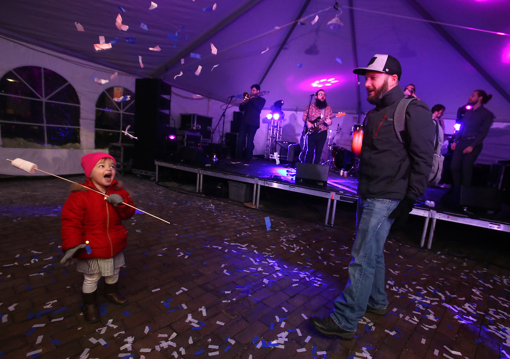 . Lowell Winterfest opening night. Audrey Lavoie, 2, of Lowell, enjoys the confetti her father Brian Lavoie tossed at the JFK Plaza music tent, where the Squires of Soul were performing. (SUN Julia Malakie)
