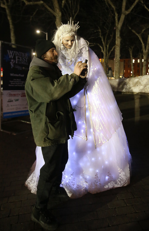 . Lowell Winterfest opening night. Snow Maiden on stilts Sasha Gaulin of Worcester poses for a photo with Sean Kelley of Lowell. (SUN Julia Malakie)